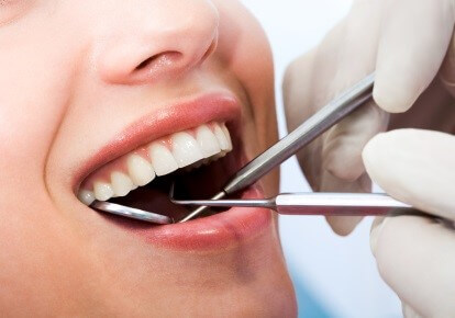 Close-up of patient's open mouth during oral inspection with mirror and hook